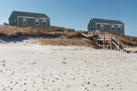 In this dune nourishment project in Massachusetts, sand was added in front of the eroded face of an existing dune and was planted with beach grass to enhance the protection provided to the house behind it. (Source: CZM)